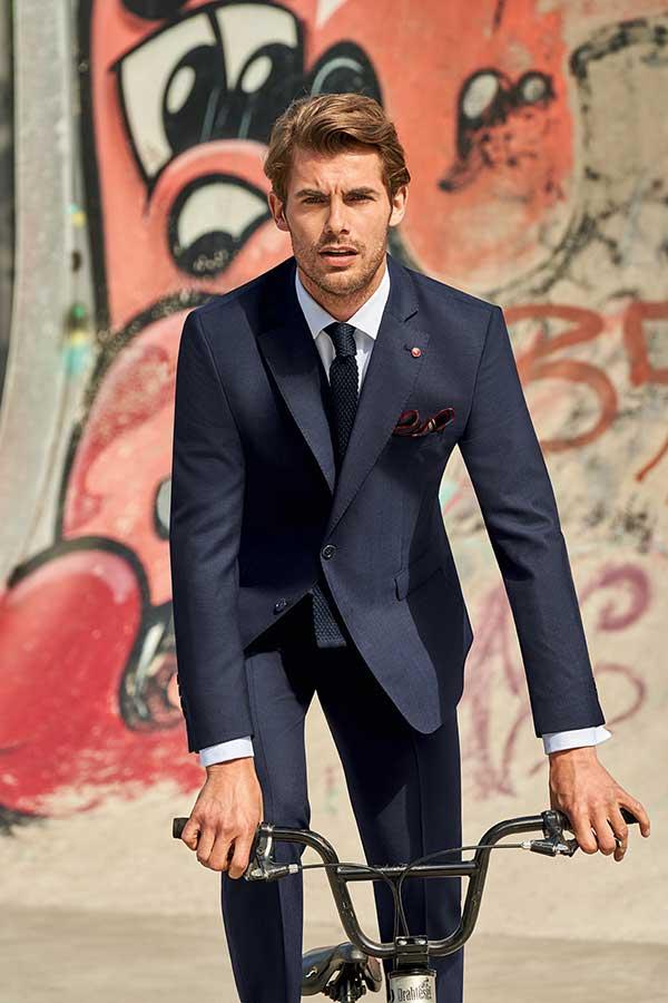 Mann im Business-Outfit von Haus der Mode in Wetzlar auf Fahrrad, Business-Anzüge Wetzlar