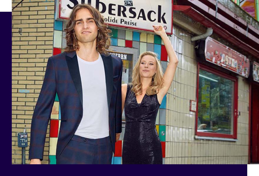 Langhaariger Mann in Anzug für Abschlussball von Haus der Mode Wetzlar und Frau in Abendkleid, festliche Anzüge Gießen
